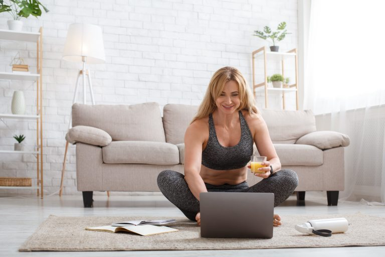 Random woman sitting at computer in fitness clothing